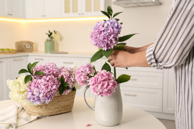 Woman making bouquet with beautiful hydrangea flowers at table indoors, closeup. Interior design element