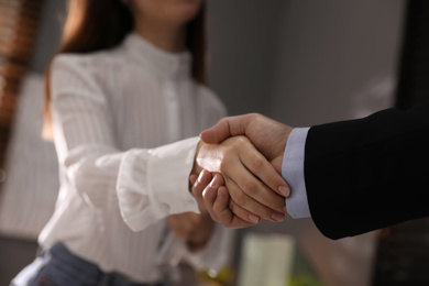 Business people shaking hands in office, closeup
