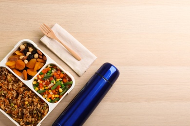 Thermos and lunch box with food on wooden background, flat lay. Space for text