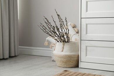 Basket with pussy willow branches near chest of drawers indoors