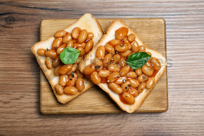 Toasts with delicious canned beans on wooden table, top view