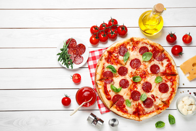 Flat lay composition with hot pepperoni pizza on white wooden table