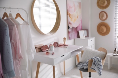 Dressing room interior with stylish makeup table, clothes and accessories