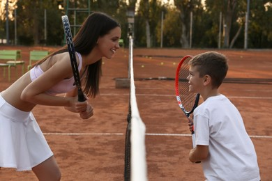 Mother with her son on tennis court