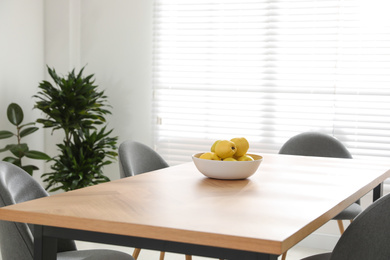 Ripe quinces on wooden table in room decorated with potted plants. Home design