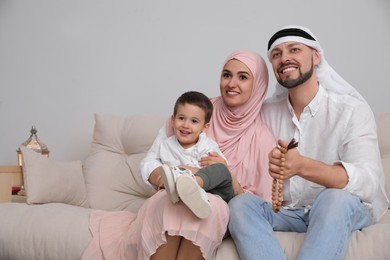 Happy Muslim family spending time together on sofa at home, space for text