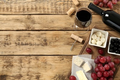 Flat lay composition with red wine and snacks on wooden table, space for text