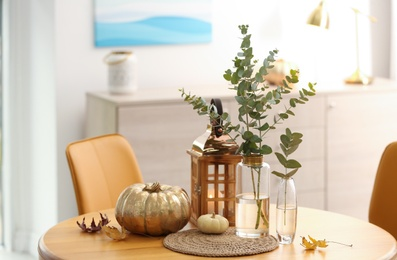 Beautiful living room interior with eucalyptus branches and decor on table