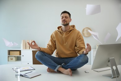 Calm man meditating on office desk in middle of busy work day