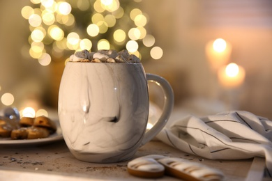 Tasty hot drink with cookies on table against Christmas lights. Space for text