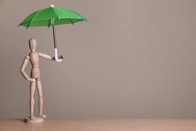 Mannequin holding small umbrella on wooden table. Space for text