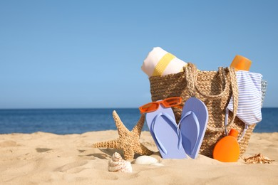 Bag and beach accessories on sand near sea. Space for text