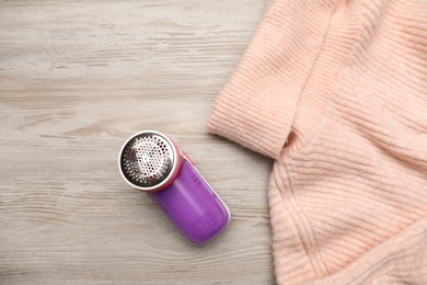 Modern fabric shaver for lint removing and sweater on wooden table, flat lay