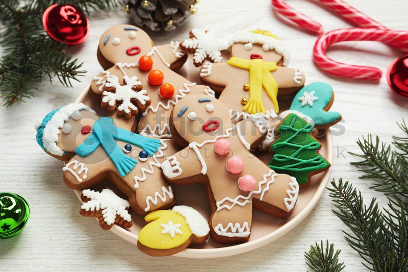 Delicious Christmas cookies and festive decor on white wooden table