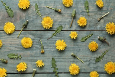 Flat lay composition with beautiful yellow dandelions on blue wooden table
