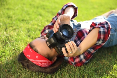 Young photographer taking picture with professional camera on green grass