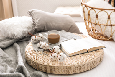 Composition with cup of drink, cotton and book on wicker pouf indoors