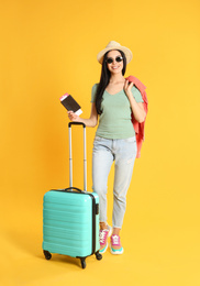 Beautiful woman with suitcase and ticket in passport for summer trip on yellow background. Vacation travel