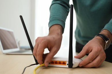 Man connecting cable to router at wooden table indoors, closeup. Wireless internet communication