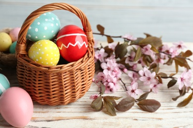 Painted Easter eggs in wicker basket and blossoming branches on wooden table