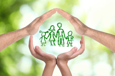 People forming house with their hands and illustration of family on blurred green background, closeup