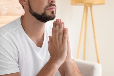 Religious man with clasped hands praying indoors, closeup. Space for text