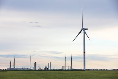 Beautiful view of landscape with wind turbine in evening. Alternative energy source