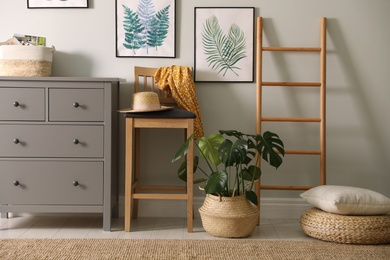 Stylish room interior with decorative ladder and monstera plant