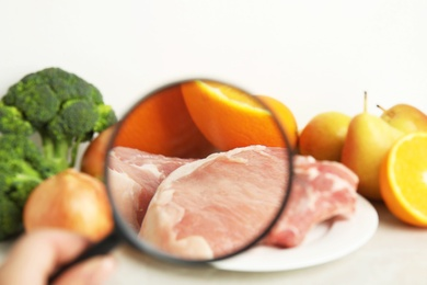 Woman with magnifying glass exploring raw meat and fruits, closeup. Poison detection