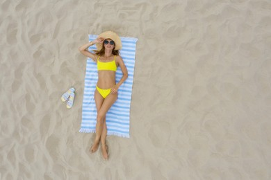 Woman sunbathing on beach towel at sandy coast, aerial view. Space for text