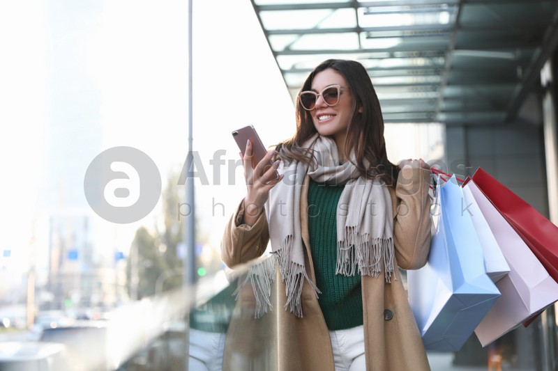 Beautiful young woman with shopping bags and smartphone outdoors