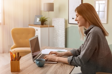 Young woman working with laptop at desk in home office