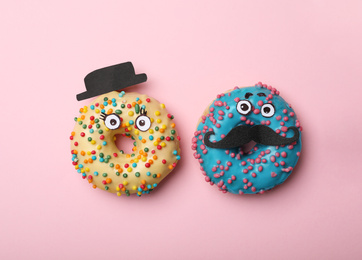 Funny faces made with donuts and paper on pink background, flat lay