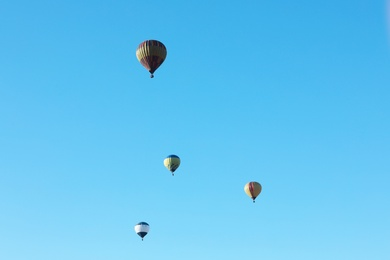 Colorful hot air balloons flying in blue sky