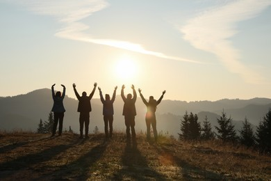 Group of people enjoying sunrise in mountains, back view