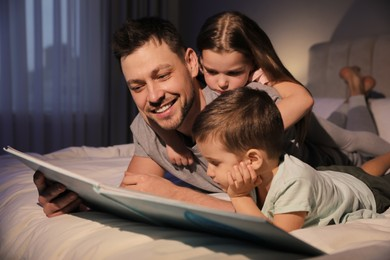 Father reading bedtime story to his children at home