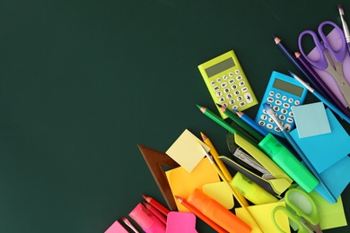 Flat lay composition with different school stationery on green chalkboard, space for text. Back to school