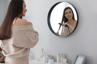 Young woman straightening hair near mirror at home. Morning routine