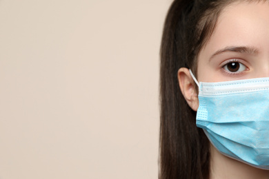 Little girl in medical mask on beige background, closeup with space for text. Virus protection
