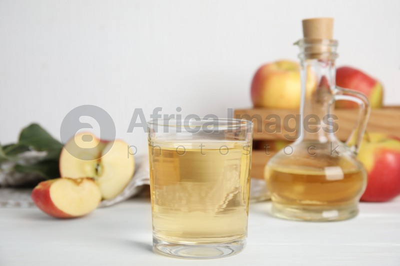 Natural apple vinegar and fresh fruits on white wooden table