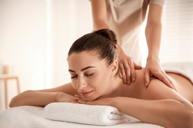 Young woman receiving shoulder massage in spa salon