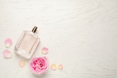 Flat lay composition with bottle of perfume and rose on white wooden background, space for text