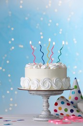 Birthday cake with burning candles and decor on white table against blurred festive lights