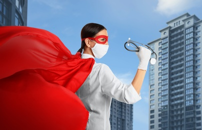 Doctor dressed as superhero on city background. Medical workers fighting with dangerous diseases