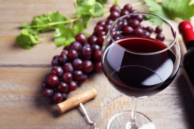 Fresh ripe juicy grapes and glass of wine on wooden table, closeup