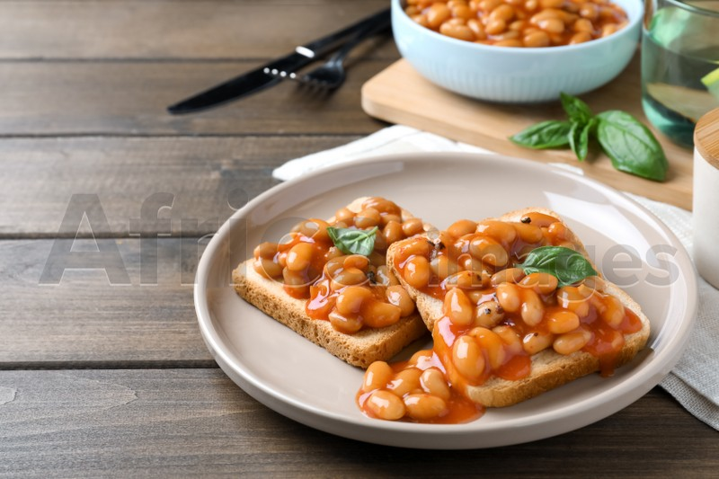 Toasts with delicious canned beans on wooden table