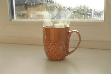 Cup of hot drink near window on rainy day