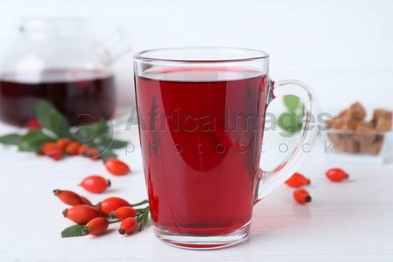 Aromatic rose hip tea and fresh berries on white wooden table, closeup