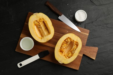 Flat lay composition with halves of fresh spaghetti squash on black table. Cooking vegetarian dish