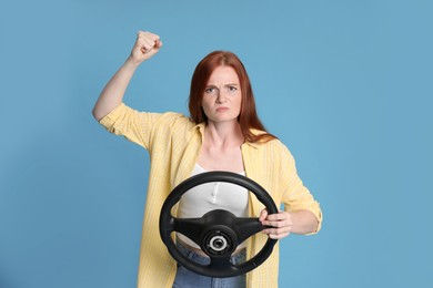 Emotional young woman with steering wheel on light blue background